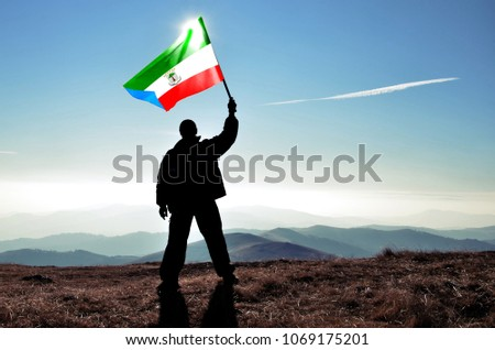 Successful silhouette man winner waving Equatorial Guinea flag on top of the mountain peak #1069175201