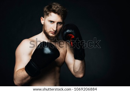 Blonde caucasian man staying on a black background with gloves in hands. #1069206884