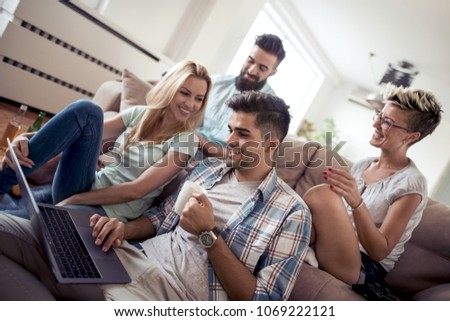 Friends sitting together on the sofa and watching funny video on laptop. #1069222121