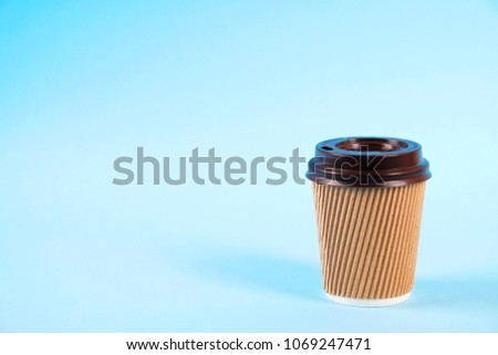 Brown disposable safe heat resistant double walled paper take out cup of coffee to go. Colorful eco-friendly cardboard mug for hot beverages, white cap on blue gradient background, close up copy space #1069247471