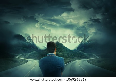 Rear view of a businessman in front of a crossroad, fork junction where a road is splitted in two different ways. Choosing the correct way between left and right, failure or success.Difficult decision #1069268519
