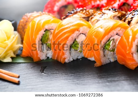 Sushi with chopsticks. Sushi roll japanese food in restaurant. California Sushi roll set with salmon, vegetables, flying fish roe and caviar closeup. Japan restaurant menu #1069272386