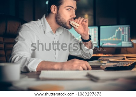 Busy businessman having late lunch eating sandwich in office working at night, stock broker trading online and eating snack looking at computer, workplace meal, overwork and food delivery concept #1069297673