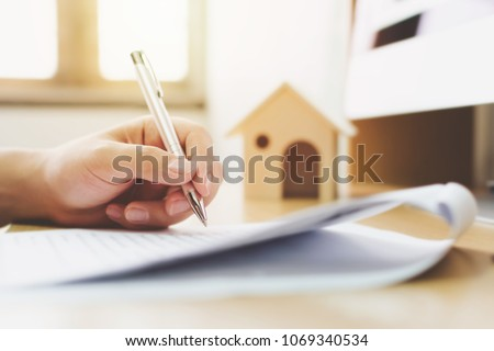 Close up hand of man signing signature loan document to home ownership. Mortgage and real estate property investment #1069340534