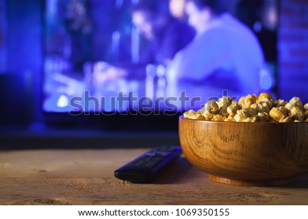 A wooden bowl of popcorn and remote control in the background the TV works. Evening cozy watching a movie or TV series at home #1069350155
