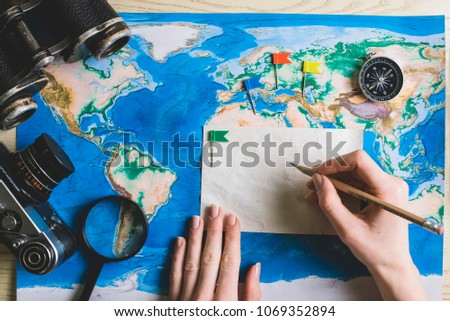 Young man hands make some notes in note book on wood background. Man hands make travel list for the future trip. Top view. #1069352894