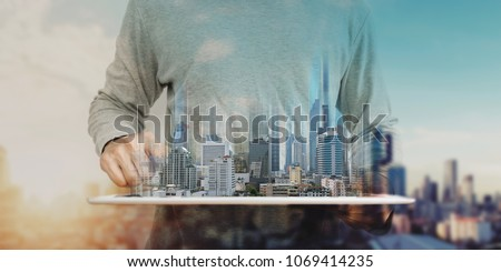 a man using digital tablet, and modern buildings hologram. Real estate business and building technology concept #1069414235