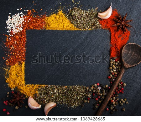 Different kind of spices on a black stone background #1069428665