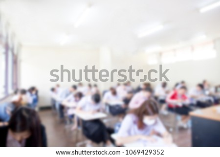 blur focus.front view abstract background of examination room with undergraduate students inside. university student in uniform sitting on lecture chair doing final exam or study in classroom. #1069429352
