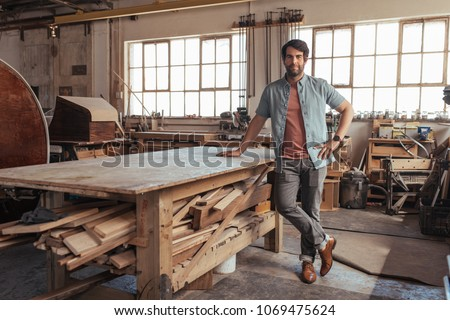 Portrait of a confident young woodworker standing next to a workbench full of wood in his carpentry workshop  #1069475624