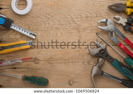 Working tools on a wooden rustic background. Top view with an empty place for inscription or advertising #1069506824