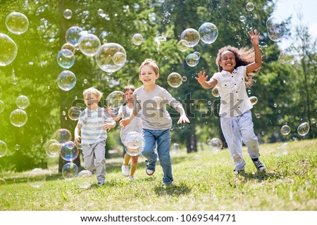 Multi-ethnic group of little friends with toothy smiles on their faces enjoying warm sunny day while participating in soap bubbles show Royalty-Free Stock Photo #1069544771