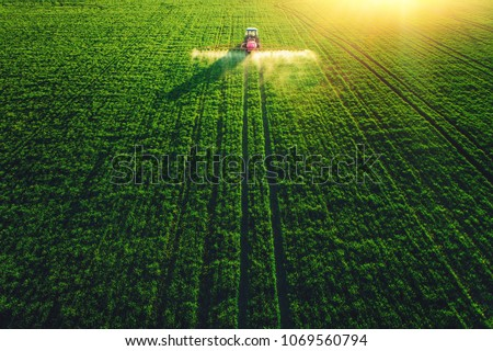 Aerial view of farming tractor plowing and spraying on field. #1069560794