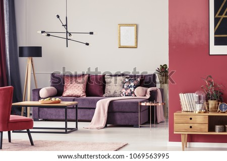 Maroon living room interior with ultra violet sofa, patterned pillows and golden frame on the wall #1069563995