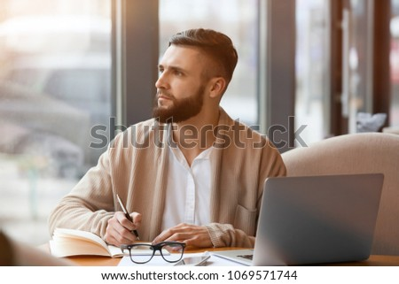 Young freelancer with laptop working in cafe #1069571744