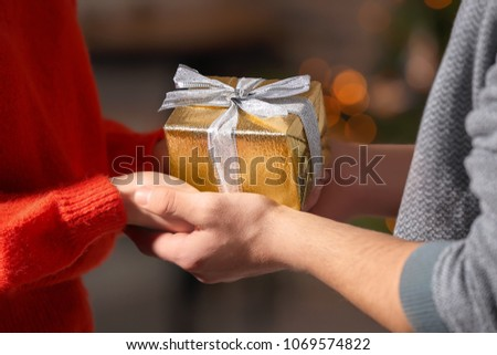 Young loving couple with gift box at home, closeup #1069574822