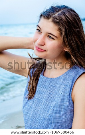 Portrait of a young beautiful girl on vacation. girl with long hair on the background of the sea. Close-up face of a happy girl on island in the ocean. happy girl in a blue dress. #1069580456