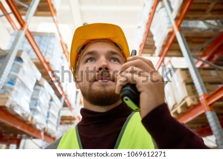 Close up portrait of young man wearing hardhat and reflective jacket speaking by walkie-talkie standing between tall shelves in warehouse, copy space #1069612271