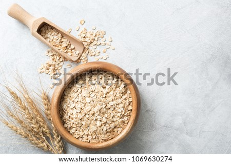 Organic rolled oats in wooden bowl on concrete background. Top view with copy space for text. Concept of healthy lifestyle, healthy eating, dieting, sport and fitness menu #1069630274