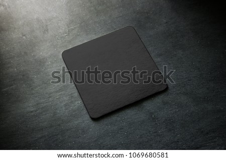 Blank black beer coaster mockup lying on grey desk. Square clear dark bar cork table-mat design mock up top side view. Quadrate cup or bottle rug display, isolated. #1069680581