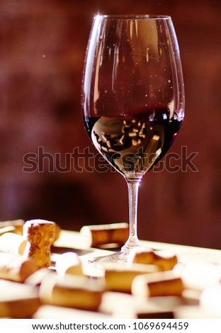 Glass of wine and corks on a wooden table in the sunlight. #1069694459