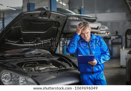 Male mechanic with clipboard near car in service center #1069696049
