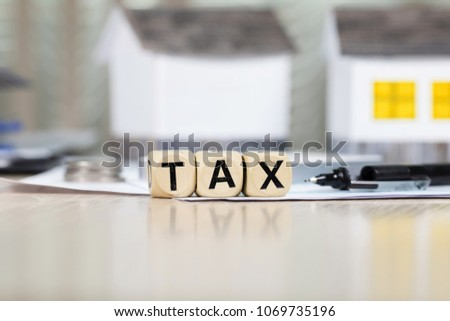 Word TAX composed of wooden letters in front of handmade house. Closeup #1069735196