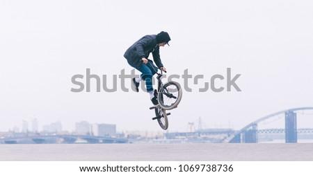 BMX rider makes a TAilwhip trick. Young man doing tricks in the air on a BMX bike. BMX freestyle #1069738736