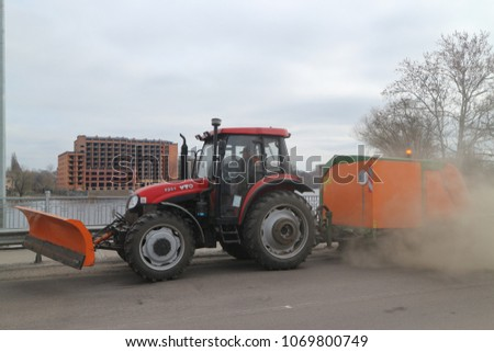 Myrgorod/Ukraine - 04.12.2018: the tractor washes and cleans dust and dirt of the streets #1069800749