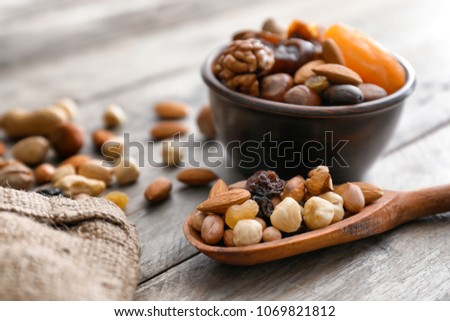 Spoon and bowl with various tasty nuts and dried fruits on wooden table #1069821812