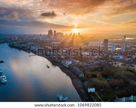 London, England - Panoramic aerial skyline view of east London at sunrise with skycrapers of Canary Wharf and beutiful colorful sky at background #1069822085