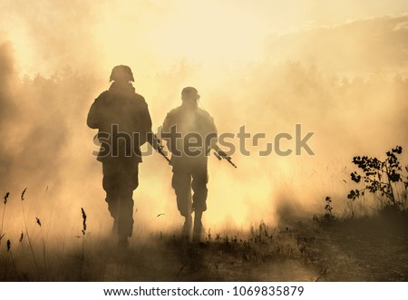 United States Marines in action. Military equipment, army helmet, warpaint, smoked dirty face, tactical gloves. Military action, desert battlefield, smoke grenades #1069835879