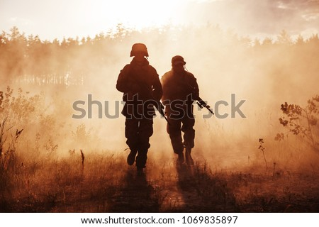 United States Marines in action. Military equipment, army helmet, warpaint, smoked dirty face, tactical gloves. Military action, desert battlefield, smoke grenades #1069835897