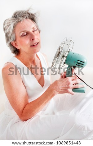 A woman having a hot flash using a fan to cool off. Royalty-Free Stock Photo #1069851443