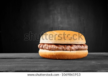 Plain beef burger on wooden table isolated on black background. #1069861913