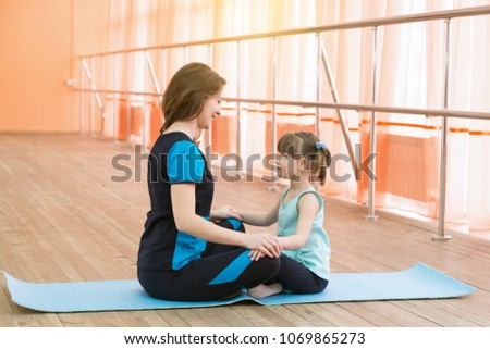 Doing sports with moms and daughters. Young woman and little girl are sitting opposite each other on a sports carpet. #1069865273