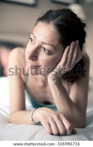 Portrait of a sensual woman lying on bed in hotel room. Shallow depth of field. #106986716