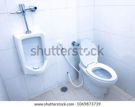 The white urinal men and white toilet bowl in the bathroom, modern and clean interior isolated in white background. #1069873739