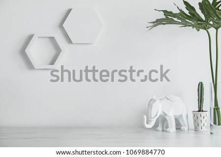 Creative desk with copy space , cacti, elephant and modern leafs. White wall with hexagone shapes. #1069884770