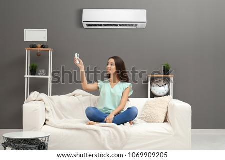 Young woman switching on air conditioner while sitting on sofa at home #1069909205
