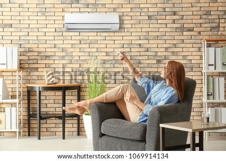 Young woman switching on air conditioner while sitting in armchair at home #1069914134