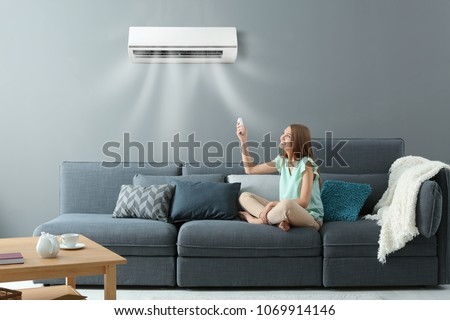 Young woman switching on air conditioner while sitting on sofa at home #1069914146