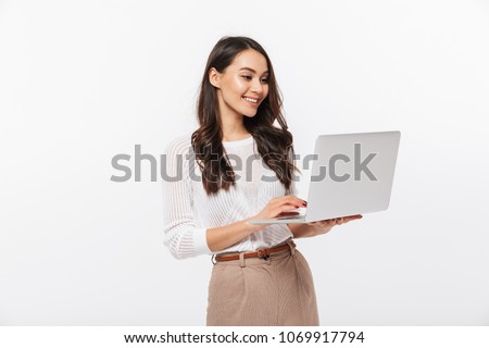 Portrait of a happy asian businesswoman working on laptop computer isolated over white background