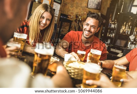 Happy friends group drinking beer at brewery bar restaurant - Friendship concept with young people enjoying time together and having genuine fun at cool vintage pub - Focus on guy - High iso image
