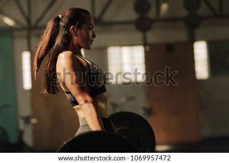 Physically fit woman lifting heavy weights. Fitness female doing heavy weight workout at gym. #1069957472