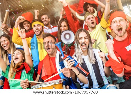 Football supporter fans friends cheering and watching soccer cup match at intenational stadium - Young people group with multicolored t-shirts having excited fun on sport world championship concept #1069957760