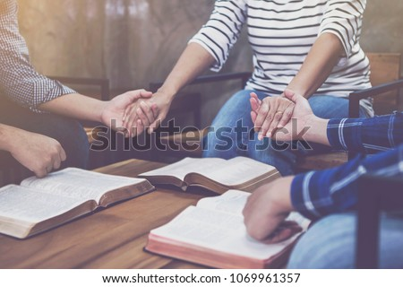 christian small group holding hands and praying together around wooden table with blurred open bible page in home room, devotional or prayer meeting concept #1069961357