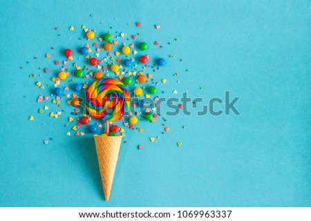 Ice cream waffle cone with colorful lollipop on stick, scattering of multicolored sweets and confectionery topping. Blue background #1069963337