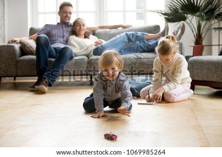 Cute kids playing while parents relaxing sofa at home together, smiling active boy entertaining with toy car near his sister on floor, happy family spending time together in living room on weekend #1069985264