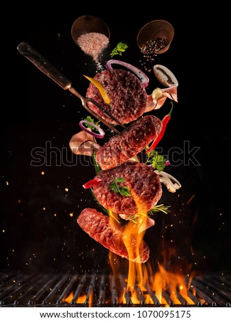 Flying pieces of beef meat pieces on hamburger from grill grid, isolated on black background. Concept of flying food, very high resolution image Royalty-Free Stock Photo #1070095175
